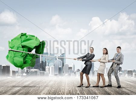 Office employees pulling together big crumpled paper ball