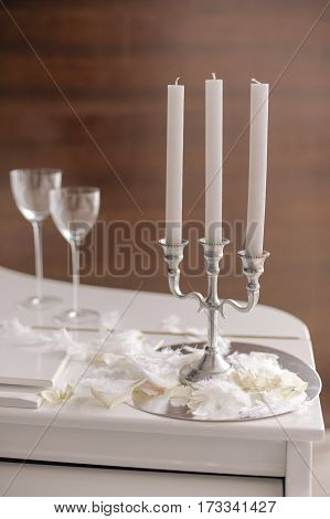 Composition with candlestick with candles and glasses and rose petals, feather and fluff