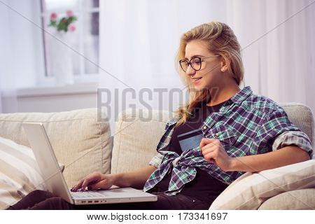 Toned of pretty lady sitting on sofa or couch and working on laptop computer. Beautiful woman holding credit card and smiling.
