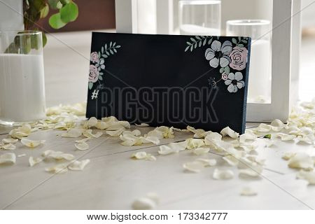Hashtag written on blackboard with bouquet of flower and birds, among candles and rose petals