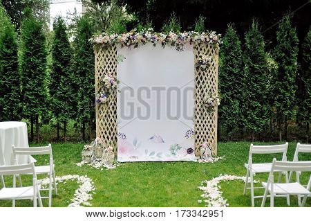 Beautiful wedding trellis decorated with white, purple and pink flowers and congratulation on banner, outdoor