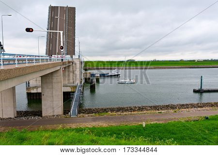 Yacht and Barge Float under the Drawbridge on the Channel in Holland