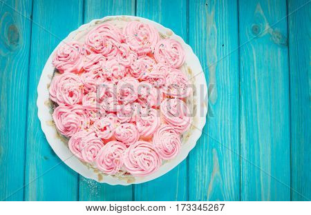 Cake with pink cream on blue wood background. Pink cake. Top view