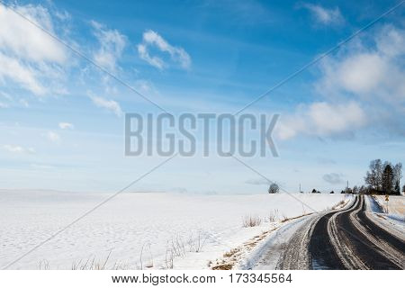 Rural road in winter time with blue and partly cloudy sky