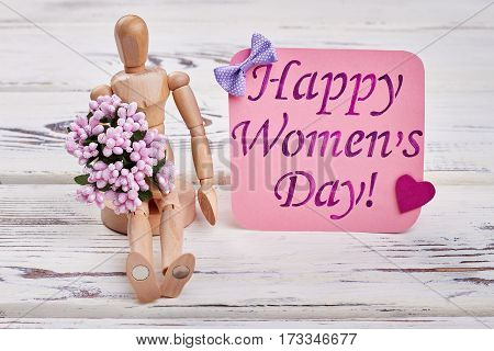Wooden manikin and flowers. Special congratulation for woman.