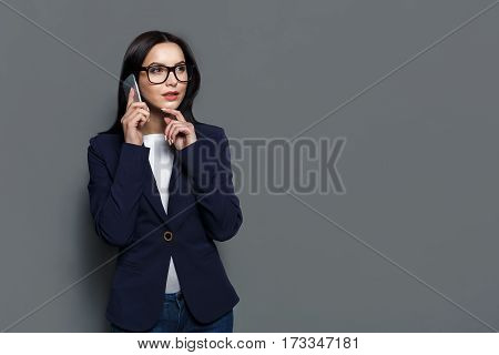 Beautiful young happy caucasian businesswoman studio shot on grey background. Thoughtful brunette woman in eyeglasses speaks on mobile phone, make call and conversation concept. Copy space