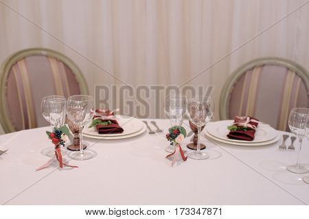 Wedding guest table, decorated with glasses and settings, in biege and dark red colours