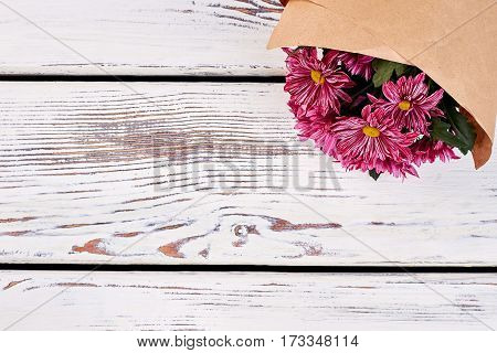 Bouquet of chrysanthemums on wood. Holiday gift guide.