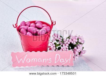 Bucket with dragee near flowers. Wishing you beautiful Women's day.