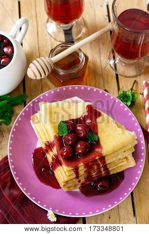 Stack of thin crepes with cherry topping for breakfast