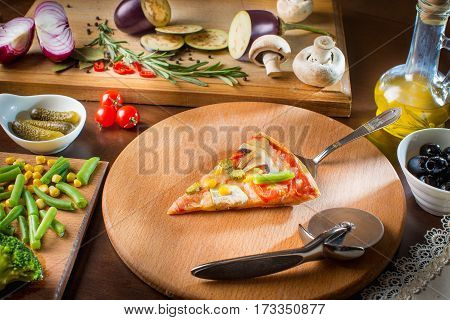 Hot pizza slice with melting cheese on a rustic wooden table. Hot Homemade Pepperoni Pizza Ready to Eat. Hot pizza slice with melting cheese on a rustic wooden table.