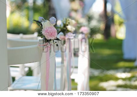 Tenderless boutonnieres on wedding chairs on each side of archway, decorated with biege and blue ribbons, closeup