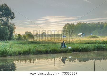 Minsk, Belarus - on July 2, 2016: fishing in the neighborhood of the city, the man catches fish on a float rod. Sunrise and fog over a polem.avtobusny stop at the road.