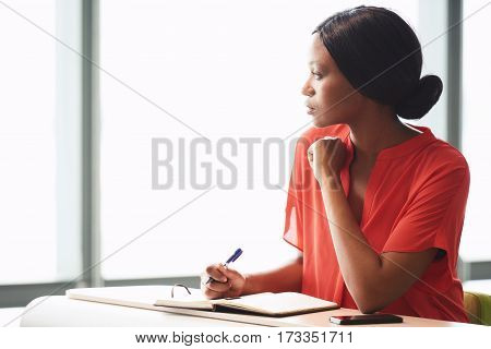 Young black businesswoman taking a little break from her work while looking out the window she is sitting next to with a pen still in her hands, while wearing a colourful orange blouse.