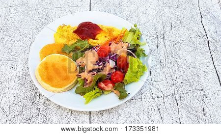 Honey Pancake and omlet with tomato sauce and vegetable salad on white dish on the wooden table