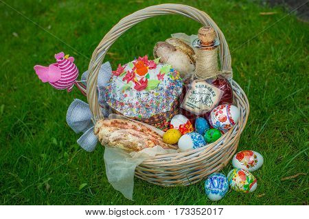 Basket of easter eggs on green grass at sunny day. Easter basket with easter eggs, easter cake and many presents on green grass. Top view.