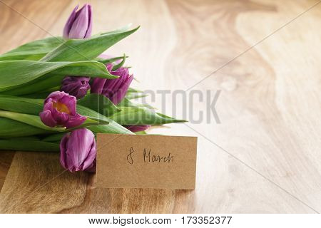 bouquet of purple tulips on wood table with 8 march greeting card shallow dof