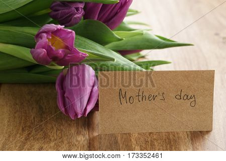bouquet of purple tulips on wood table with mothers day paper card, shallow dof