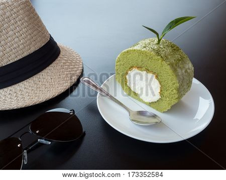 Close-up image of green tea roll cake with tea leave sunglasses and woven hat on table. Copy space