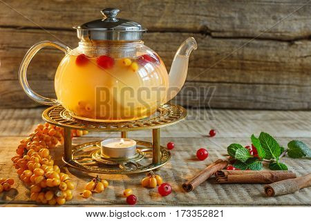 Glass tea pot with hot tasty tea with lemon, herbs and many red, yellow berries,. Berries, greens, mint and tea. Tea pot on warm colors on wooden background. Hot tasty tea wit mint