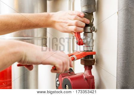 closeup of plumber hands working with pipeline connections
