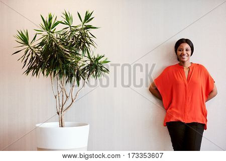 Black female wearing a bright orange blouse while smiling at camera and standing next to a tree planted in a pot as a sign of support for the environment.