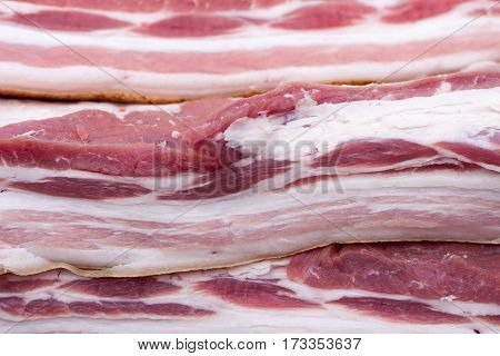 pieces of raw bacon as background, close-up. Selective focus.