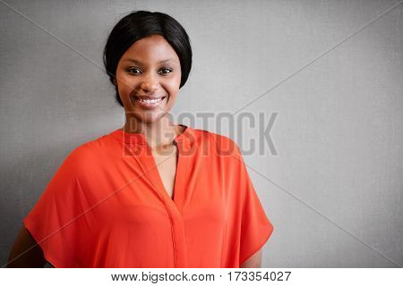 Portrait of black businesswoman smiling at camera while wearing a bright orange blouse while standing against a textured grey wall.