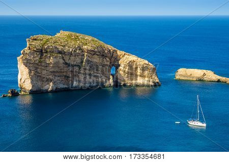 Gozo Malta - The amazing Fungus Rock at Dwejra bay with sailboat blue sea water and sky on a beautiful summer day