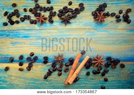 coffee beans cinnamon sticks and star anise on wooden background painted in blue and gold. place for text.