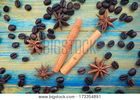 coffee beans cinnamon sticks and star anise on wooden background painted in blue and gold. close-up.