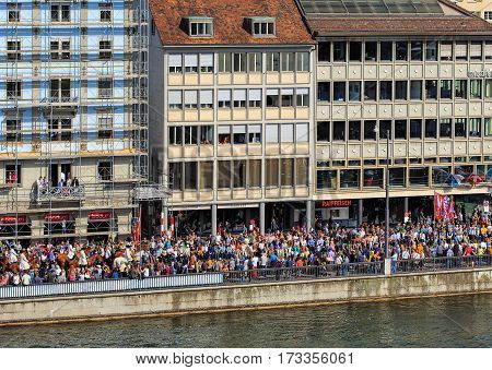 Zurich, Switzerland - 13 April, 2015: people on the embankment of the Limmat river during the Sechselauten celebration. The Sechselauten is a traditional spring holiday in the city of Zurich.