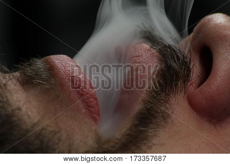 Young man breathe cigarette smoke/ This is a detail man face.