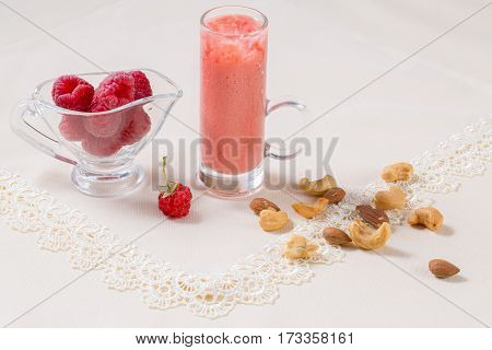 Beautiful appetizer pink raspberries fruit smoothie or milk shake in glass jar with berries background, top view. Yogurt cocktail. Close up. Natural detox. Liquid ice cream. Raspberry Smoothie.