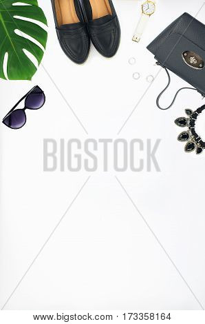 Overhead view of women's fashion set of accessories isolated on white background. Top view of leather bag shoes sunglasses and watch
