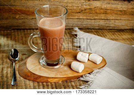 Coffee with milk isolated on wooden background with spoon and zephyr. Coffe with milk. Hot tasty latte with milk. Coffee, Milk and Sugar. Coffee with milk, coffee maker, coffee beans, dark toned image