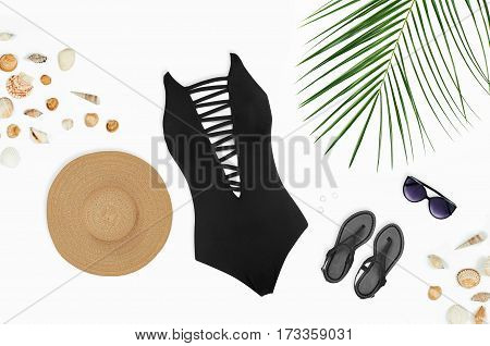 Beach accessories: swimsuit sunglasses hat sandals with palm branches and shells. Top view on white background