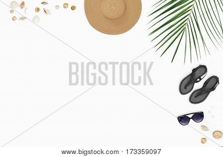 Flat lay beach accessories: sunglasses hat sandals with palm branches and shells. Top view on white background. Composition with space for copy