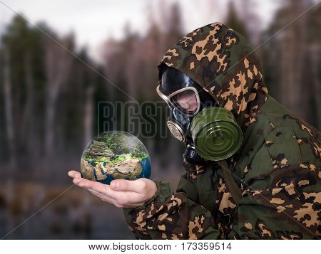 Man in a military uniform and a gas mask holds in his hands the globe.