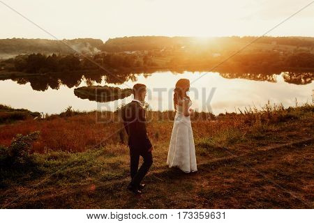 Romantic Landscape, Newlywed Couple Posing At Sunset Field Near A Lake, Handsome Groom Walking Towar
