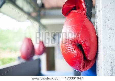Red Muay Thai Boxing Gloves Hanging On Corner Of  Boxing Ring In Camp