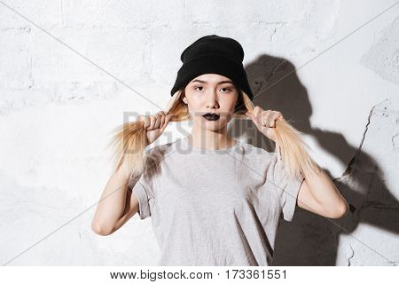 Serious Hipster in black hat holding her hair and looking at camera over gray background