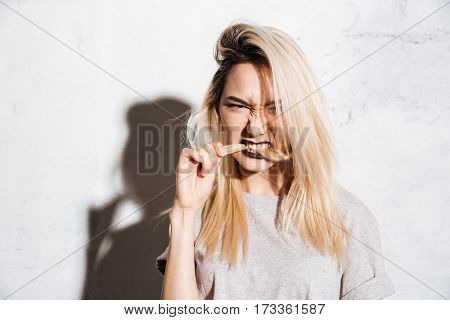 Angry beautiful young woman biting her long blonde hair over white background