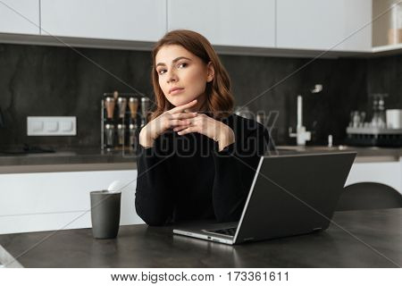 Photo of young amazing woman dressed in black sweater sitting at kitchen. Chatting by laptop. Looking at camera.