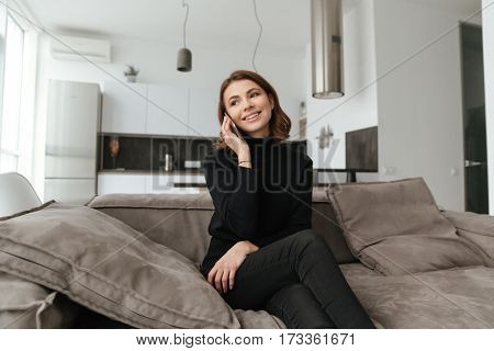 Photo of young cheerful woman dressed in black sweater sitting on sofa at kitchen. Talking by mobile phone.