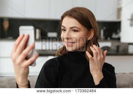 Picture of young pretty woman dressed in black sweater sitting on sofa at kitchen. Take a selfie by mobile phone.