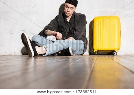 Hipster in snap back sitting on the floor near the wall with suitcase and looking at wristwatch