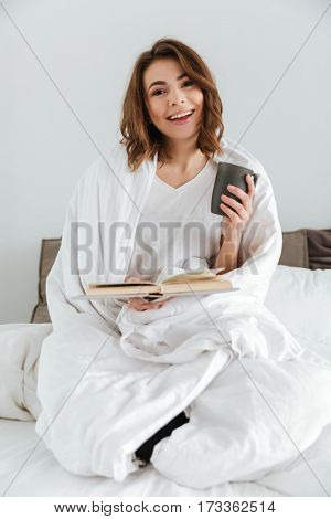 Picture of young pretty lady dressed in white t-shirt sitting on bed at home indoors while reading book and drinking coffee.