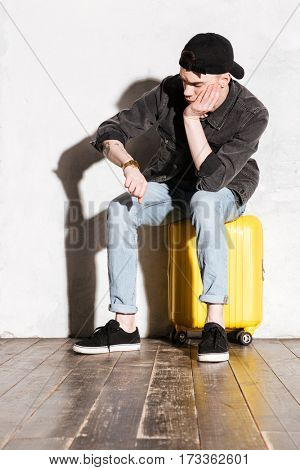Vertical image of Hipster in snap back sitting on suitcase, waiting and looking at wristwatch
