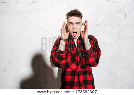 Shocked hipster in red shirt which holding hand near the head and looking at camera